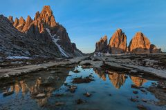 Tre cime di Lavaredo at sunrise, Dolomite Alps, Italy. Tre cime di Lavaredo reflected from a lake, Dolomite Alps, Italy Royalty Free Stock Image