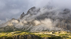 Tre Cime Shrouded in Clouds. Tre Cime in the Dolomites in Northern Italy shrouded underneath clouds at sunset Royalty Free Stock Images