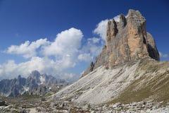 Tre Cime-Spitzen, umgebende Berge und Wolken Stockbild