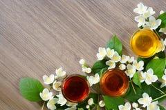 Tre ciotole di gelsomino di fioritura del ramo e del miele su un fondo di legno Vista da sopra fotografia stock libera da diritti