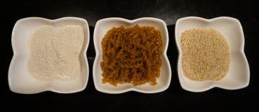Tre ciotole di prodotti di tef (erba di mazzo, taf, farina annuali di xaafii) su un fondo nero Fotografia Stock