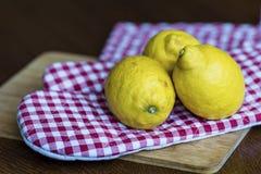 Tre citroner på rutig röd dishtowel Royaltyfri Fotografi
