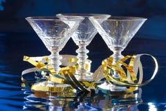 Tre coctailexponeringsglas med guld- slingrande royaltyfri bild