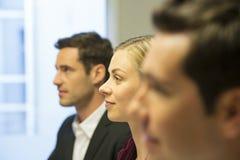 Tre colleghi che si siedono ad una riunione d'affari, fuoco sopra abbastanza Immagine Stock