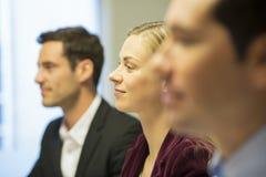 Tre colleghi che si siedono ad una riunione d'affari, fuoco sopra abbastanza Fotografie Stock