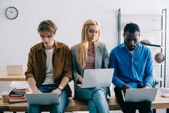 tre colleghi multiculturali di affari che per mezzo dei computer portatili e sedendosi sulla tavola in moderno fotografia stock libera da diritti