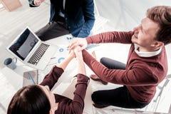 Tre colleghi ottimisti che puntano su successo immagine stock