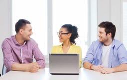 Tre colleghi sorridenti con il computer portatile in ufficio Immagine Stock