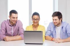 Tre colleghi sorridenti con il computer portatile in ufficio Immagini Stock