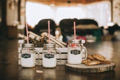 Tre contenitori di latte e dei biscotti Fotografie Stock
