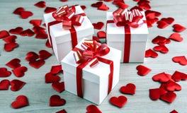 Tre contenitori di regalo bianchi su un fondo e su un cuore grigi del tessuto SH Fotografie Stock