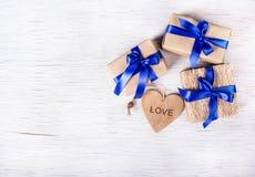 Tre contenitori di regalo con i nastri blu e biglietti di S. Valentino da un albero su un fondo bianco Giorno del `s del bigliett Fotografia Stock