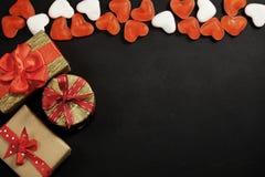 Tre contenitori di regalo con le caramelle rosse con lo spazio della copia sul nero Fotografie Stock Libere da Diritti