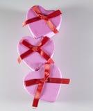 Tre contenitori di regalo a forma di del cuore rosa Immagini Stock