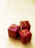 Tre contenitori di regalo rossi su una priorità bassa dorata Fotografia Stock