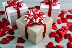 Tre contenitori di regalo sulle forme del cuore del tessuto e di un fondo grigio Immagini Stock