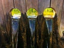 Tre correnti di acqua che cadono attraverso un pannello di legno Fotografie Stock