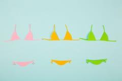 Tre costumi da bagno di carta variopinti del bikini su fondo blu minimi Immagini Stock