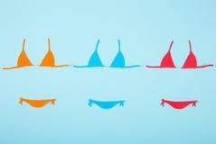 Tre costumi da bagno di carta variopinti del bikini su fondo blu minimi Fotografia Stock Libera da Diritti