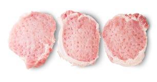 Tre cotolette crude della carne di maiale Fotografie Stock