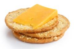 Tre cracker dorati del formaggio su bianco Fotografie Stock