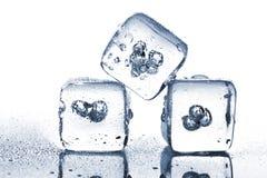 Tre cubetti di ghiaccio di fusione con la rugiada dell'acqua fotografia stock
