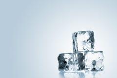 Tre cubetti di ghiaccio impilati sopra il fondo blu di pendenza Immagini Stock