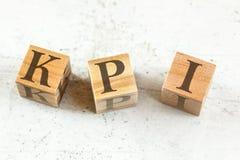 Tre cubi di legno con le lettere KPI corrisponde all'indicatore di efficacia chiave sul bordo bianco fotografia stock