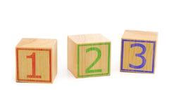 Tre cubi di legno marroni hanno allineato in una fila con i numeri uno, due Immagine Stock Libera da Diritti