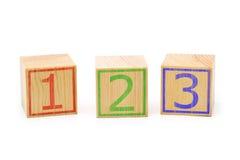 Tre cubi di legno marroni hanno allineato in una fila con i numeri uno, due Fotografie Stock