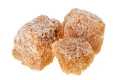 Tre cubi marroni dello zucchero di canna del grumo Fotografie Stock