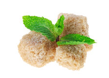 Tre cubi marroni dello zucchero di canna del grumo con menta peperita Immagini Stock