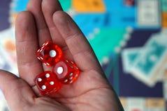 Tre cubi rossi dei dadi sulla palma sopra il gioco da tavolo Immagine Stock Libera da Diritti