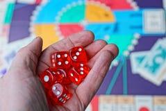 Tre cubi rossi dei dadi sulla palma sopra il gioco da tavolo Fotografia Stock