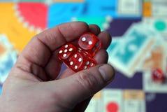 Tre cubi rossi dei dadi sulla palma sopra il gioco da tavolo Immagine Stock