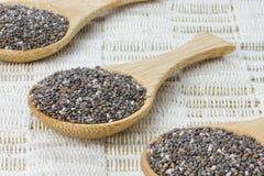 Tre cucchiai di legno con i semi neri di chia Immagini Stock Libere da Diritti