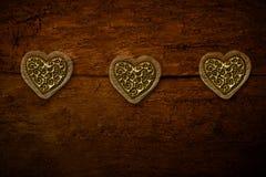 Tre cuori dell'oro su vecchio fondo di legno Fotografia Stock Libera da Diritti