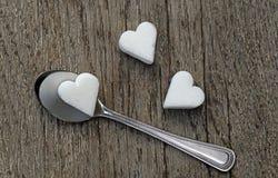 Tre cuori dello zucchero bianco con un cucchiaino su fondo di legno Fotografia Stock Libera da Diritti