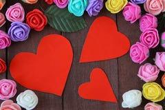 Tre cuori e fiori rossi su un legno marrone del fondo Fotografie Stock