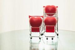 Tre cuori rossi messi in due carretti del metallo come oggetto di vendita immagine stock