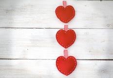 Tre cuori rossi si trovano sui precedenti di legno bianchi Fotografie Stock Libere da Diritti