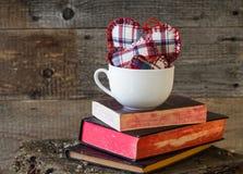 Tre cuori si imbarcano sui libri di tazza bianchi Fotografie Stock