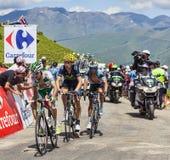 Tre cyklister på sänkan de Val Louron Azet Arkivbild