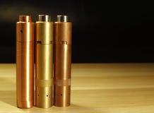 Tre d'ottone e mods meccanici di rame per vaping sigaretta elettronica sulla superficie di legno sulla fine nera del fondo su Fotografie Stock Libere da Diritti