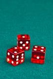 Tre dadi di colori rossi su verde Immagini Stock Libere da Diritti