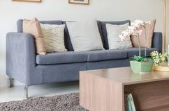 Tre dei cuscini sul sofà blu scuro in salone moderno Fotografie Stock
