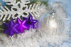 Tre dekorativa violetta leksaker av en snöflinga och ett silvrigt nytt år klumpa ihop sig Royaltyfria Foton