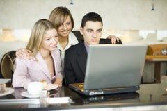 Tre della gente di affari al computer portatile Immagini Stock