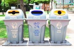 Tre di riciclano la pattumiera in parco pubblico Immagine Stock