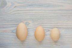 Tre dimensioni differenti delle uova Immagini Stock
